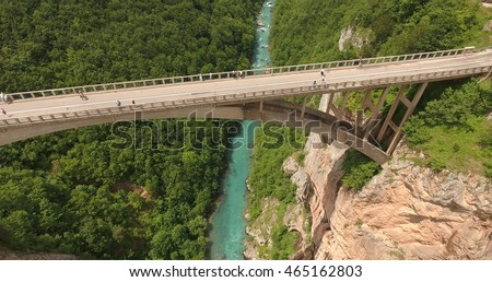 Aerial side view of Durdevica bridge with group of people walking and photographing Tara river canyon. Montenegro, Europe