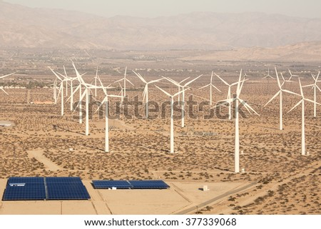 Aerial Solar Farm and Turbines in California Desert Aerial Solar panels energy in a California desert at sunset with mountains in the background. Sunlight, solar panels and wind turbines.  - stock photo