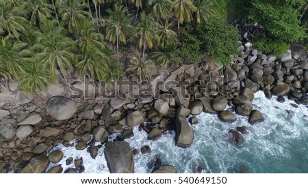 Aerial top view of sea waves hitting rocks on the beach in Phuket, Thailand