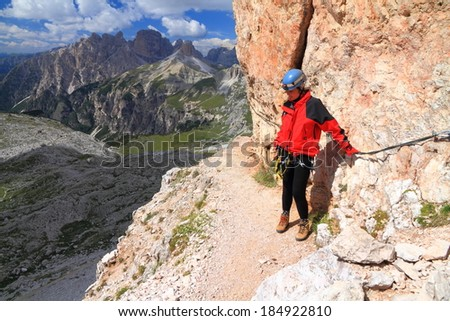 Aerial trail and a via ferrata climber gripping the steel cable, Dolomite Alps, Italy