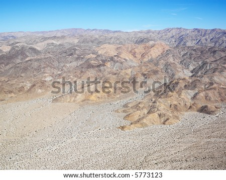 Aerial veiw of remote California desert with mountain range in background.