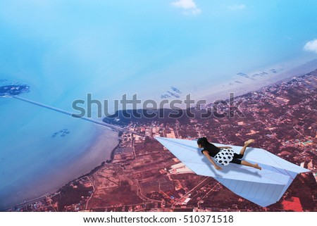 Aerial view a girl flying on paper plane.