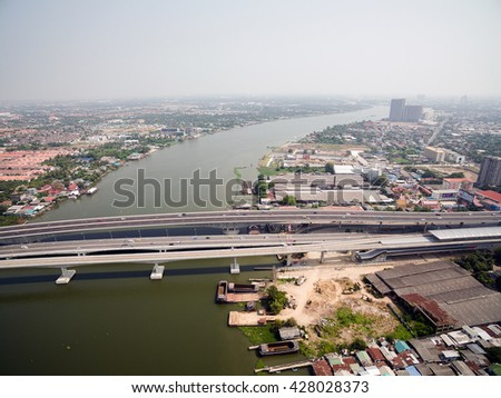 Aerial view above Chao Phraya River, the Expressway and Purple Line MRT Skytrain in Tiwanon area, Nonthaburi, Thailand