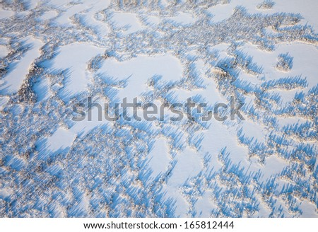 Aerial view above the boundless tundra in winter. Marshes are covered snow under cloudy sky.  - stock photo