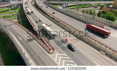 Aerial view at lines of city highway. Semitrailer trucks and cars drive on roads in small traffic jam. Russia
