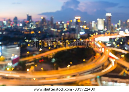 Aerial view city road intersection during twilight, blurred bokeh light background - stock photo