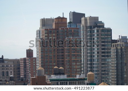 Aerial view establishing photo overlooking New York City apartment buildings in midtown Manhattan on a bright blue sky day