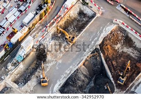 Aerial view excavators and tipper trucks working at construction. Hong Kong - stock photo