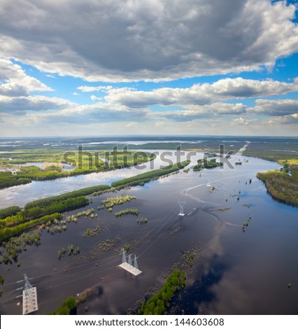Aerial view flooded forest plains with power lines. - stock photo