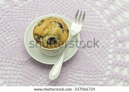 Aerial view focus on a ready to serve freshly baked blueberry muffin in souffle paper cup and a silver. Bokeh background of light purple lacy table cloth on white top. - stock photo