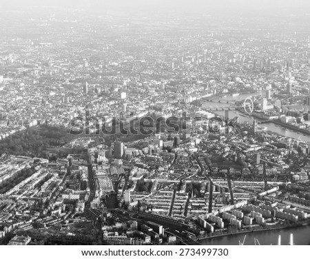 Aerial view from a flying plane in the sky over London city in black and white - stock photo