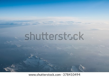 Aerial view from airplane flying above white abstract clouds and mountains ridge - stock photo