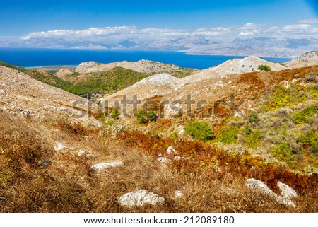 Aerial view from Pantokrator mountain foothill to the Albania mountains over colorful foliage and sea, Corfu, Greece - stock photo