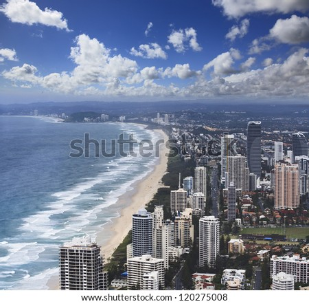 aerial view from Surfer's paradise Q1 skyscrapers on the city building towers, coastline with sand, surf and beach under blue sky - stock photo