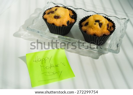 Aerial View Happy Mother's Day with cupcakes and text message  Appreciation green sticky note greeting card with butter pastry cakes with raisins on vintage glass plate, white natural light background - stock photo