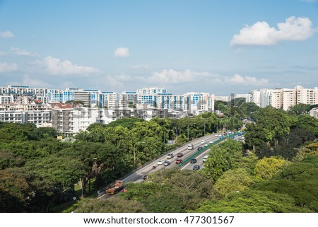 Aerial view HDB housing complex near highway with lot of green trees and vehicles in traffic, cloud blue sky. Singapore is an excellent green, clean city. Asia transportation, infrastructure concept.
