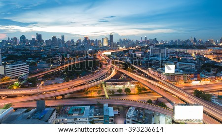 Aerial view highway intersection with city downtown background during twilight - stock photo