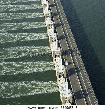 Aerial view in the late evening of the Oosterscheldekering, a storm surge barrier which is part of the delta works to protect Holland from high sea level - stock photo