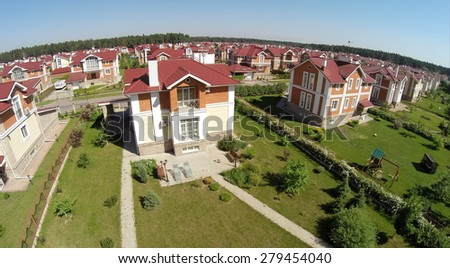 Aerial view many similar houses in gated development at sunny summer day. - stock photo