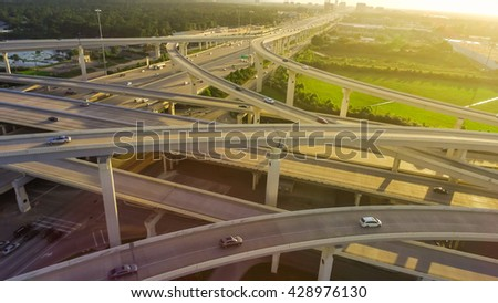 Aerial view massive highway intersection, stack interchange with elevated road junction overpass at late afternoon in Houston, Texas. This five-level freeway interchange carry heavy traffic, panorama. - stock photo