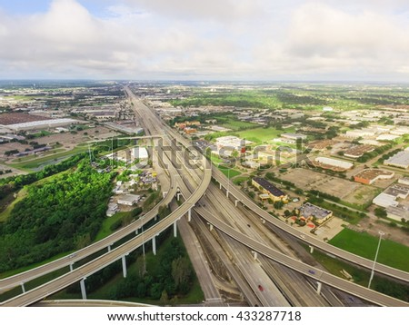 Aerial view massive highway intersection, stack interchange with elevated road junction overpass at early morning in Houston, Texas. This five-level freeway interchange carry heavy rush hour traffic. - stock photo