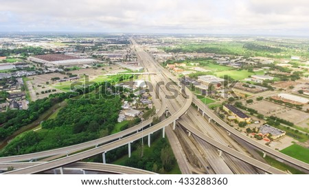 Aerial view massive highway intersection, stack interchange with elevated road junction overpass at early morning in Houston, Texas. This five-level freeway interchange carry heavy traffic, panorama.