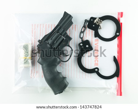 aerial view of a bag marked evidence containing a roll of money, a revolver and a pair of handcuffs with their keys, on a white background - stock photo