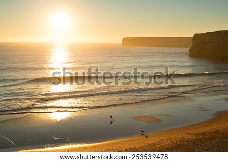 Aerial view of a beach with surfers at sunset in Portugal. - stock photo