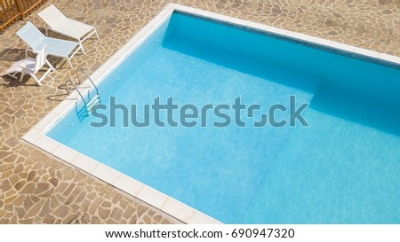 aerial view of a blue pool with stairs to descend and climb into the water