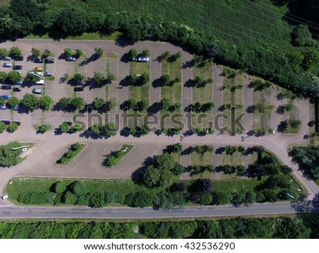 Aerial view of a car park with green trees