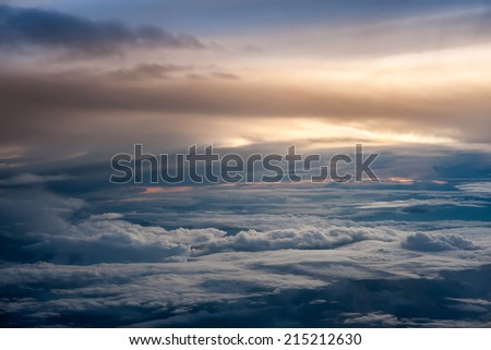 Aerial view of a cloudy sunset while flying above the clouds - stock photo
