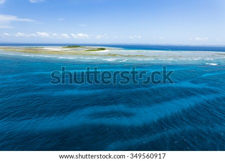 Aerial view of a deserted tropical island and coral reefs with clear blue water, Okinawa, Japan