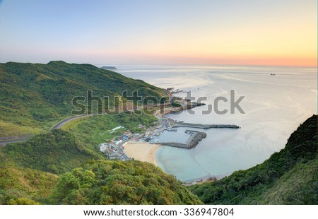 Aerial view of a fishing village at dawn on northern coast of Taipei Taiwan ~ A coastal highway along beautiful coastline and a fishing village in golden sunlight - stock photo