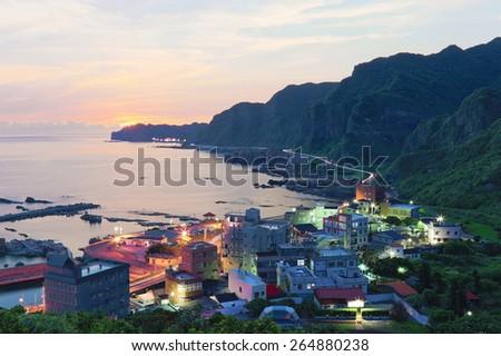 Aerial view of a fishing village at dawn on northern coast of Taipei Taiwan ~ Beautiful coastal landscape under moody sunrise sky - stock photo