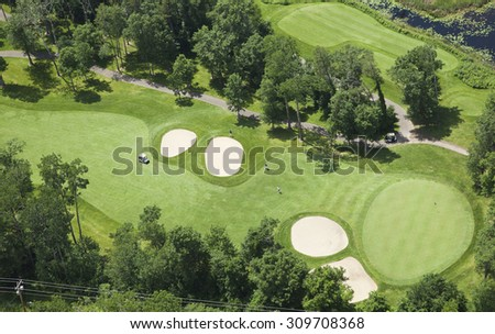 Aerial view of a golf course fairway and green with sand traps, trees and golfers - stock photo