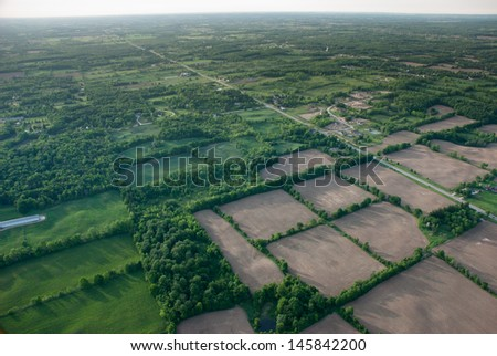 Aerial view of a grean rural area under a long horizon. - stock photo