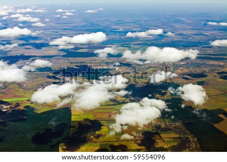 Aerial view of a green rural area under cloudy sky - stock photo