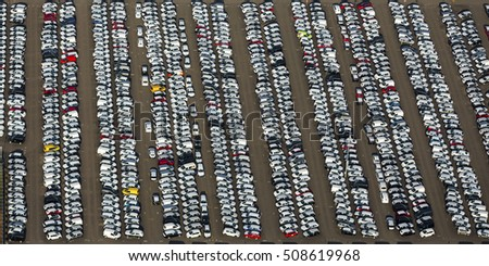 Aerial view of a huge parking place with more than hundreds of cars at a car dealership in The Netherlands