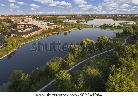 Aerial view of a lake beside a community center with walking paths and bridge in The Glen, Glenview, Illinois.