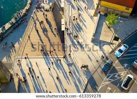 Aerial view of a people walking on the street at sunset
