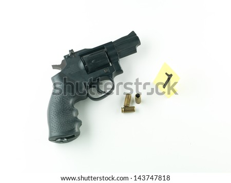aerial view of a revolver with a bullet and a shell casing and a number one evidence marker beside it, against a white background - stock photo