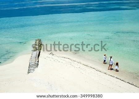 Aerial view of a tropical coast with mother and kids enjoying beach vacation - stock photo