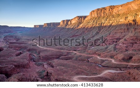 aerial view of a windy road through red sandstone canyon with coarse vegetation near Moab, Utah - stock photo