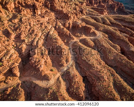 aerial view of a windy 4WD road through red sandstone canyon with coarse vegetation near Moab, Utah - stock photo