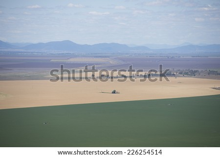 Aerial view of agricultural farmland in New South Wales, Australia, with fields and meadows of crop and wheat, mountain range in blurred background and copy space. - stock photo