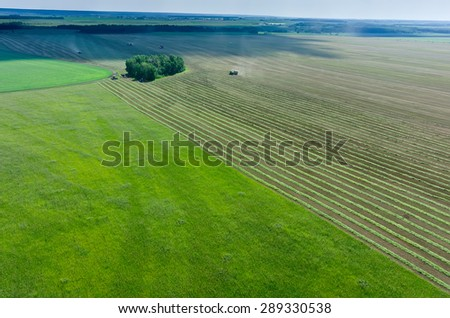 Aerial view of agricultural fields with working harvester - stock photo