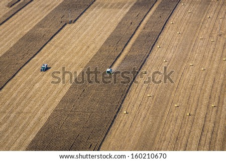 Aerial view of agricultural land with harvester - stock photo
