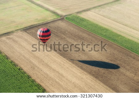 Aerial view of an hot air balloon and its shadow nearly grounded over fields - stock photo
