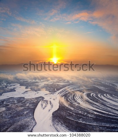 Aerial view of an orange sunrise over the forest river during winter. - stock photo