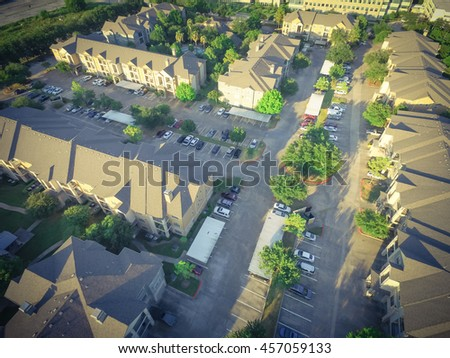 Aerial view of apartment garage with full of covered parking, cars and green trees of multi-floor residential building at sunset in US. Urban infrastructure and transportation concept. Vintage filter.